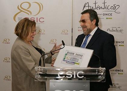 Rosa Menéndez y Miguel Carballeda, con una lámina enmarcada del cupón dedicado al 80 aniversario del CSIC