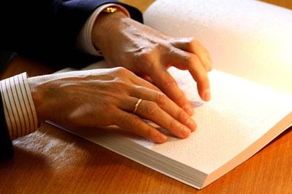 Manos de hombre leyendo braille