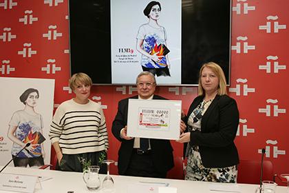 Carmen Bayarri y Manuel Gil sostienen la copia enmarcada del cupón que la ONCE dedica a la Feria del Libro, en presencia de Sara Morante, autora del cartel