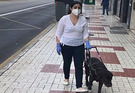 Una mujer ciega circula con su perro guía durante el estado de alarma dotada con mascarilla