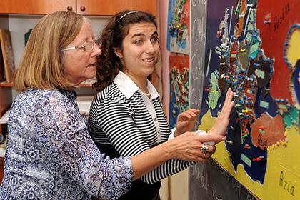 Una mujer ciega toca un mapa en relieve, acompañada de una profesora