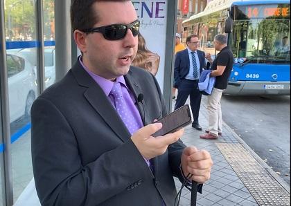 Moovit usado por una persona ciega en una parada de autobús
