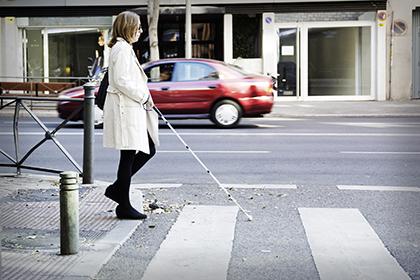 Una mujer ciega, con su bastón blanco, cruza un paso de cebra