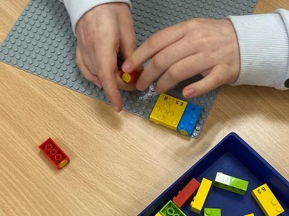 manos de un niño ciego con las piezas de LEGO Braille
