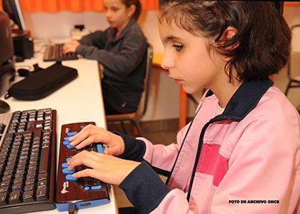 Una niña ciega utilizando el ordenador con línea braille en el aula
