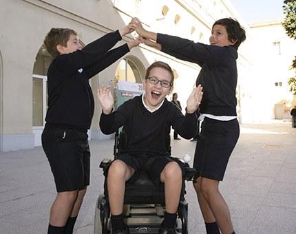 Alumno en silla de ruedas jugando en el patio con sus compañeros