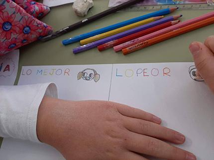 Manos de un alumno escribiendo en un folio sobre el 37 Concurso Escolar del Grupo Social ONCE