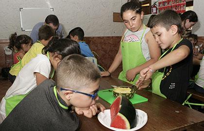 Varios chavales preparan sus recetas durante el campamento de verano