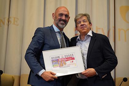 Joaquín Goyache, a la izquierda, y Antonio Mayor, con una lámina enmaracada del cupón dedicado al 30 aniversario de Servimedia