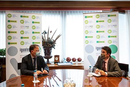 Enrique Cortés y Andrés Ramos charlan en la mesa durante la firma de un convenio