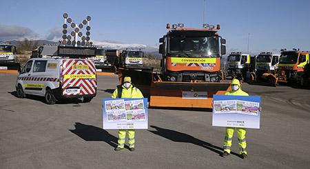 Dos miembros del equipo de conservación de carreteras de la DGT con las láminas de los cupones