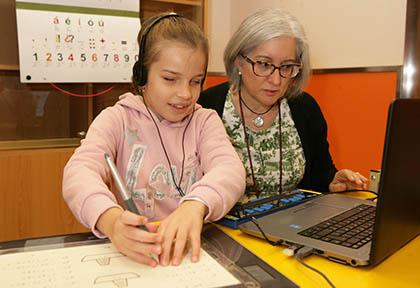Una alumna ciega trabaja en el ordenador junto a su profesora