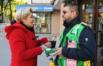 Un vendedor de la ONCE con chaleco y TPV atiende a una clienta