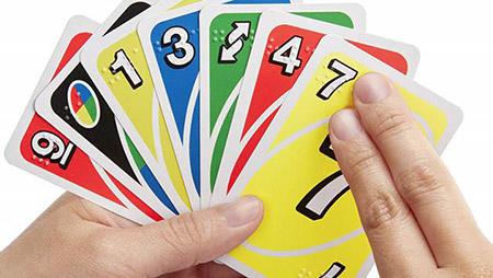 Imagen de unas manos tocando las cartas de UNO Braille