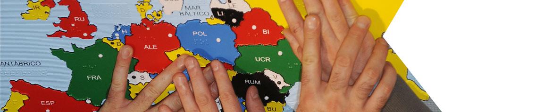 diversas manos sobre un mapa mundi en braille
