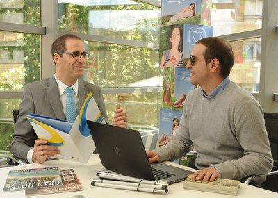 Una persona ciega en su puesto de trabajo junto a un compañero