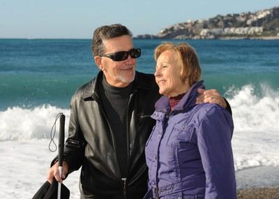 Una pareja de afiliados mayores delante de una playa
