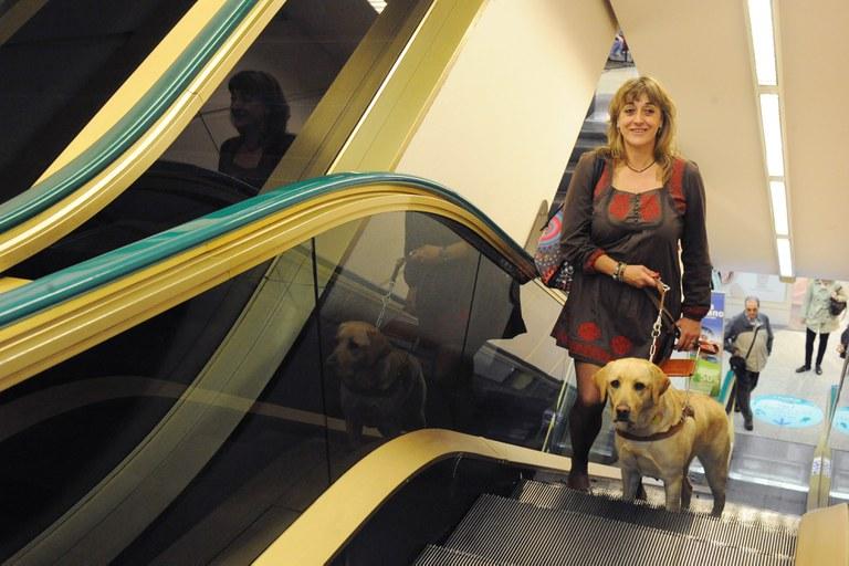 Una usuaria ciega sube las escaleras del metro junto a su perro guía