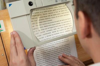 Una persona ciega lee ayudado de una telelupa