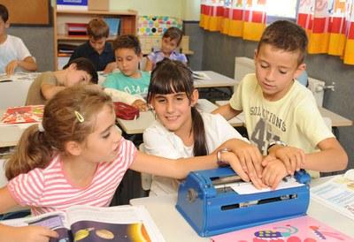 Una niña enseña a sus compañeros de aula la máquina Perkins