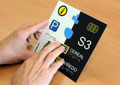 Una persona ciega lee un cartel adaptado a braille