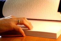 Imagen de unas manos leyendo un libro en braille